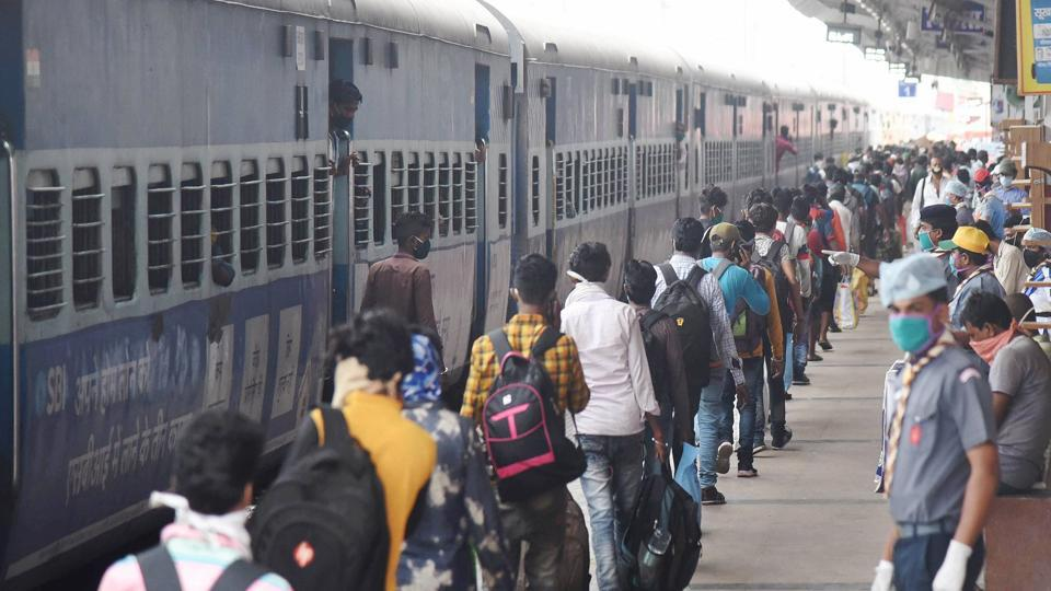 Migrants, maintaining social distancing, stand in a queue after deboarding 'Shramik Special' train at Danapur railway station near Patna.