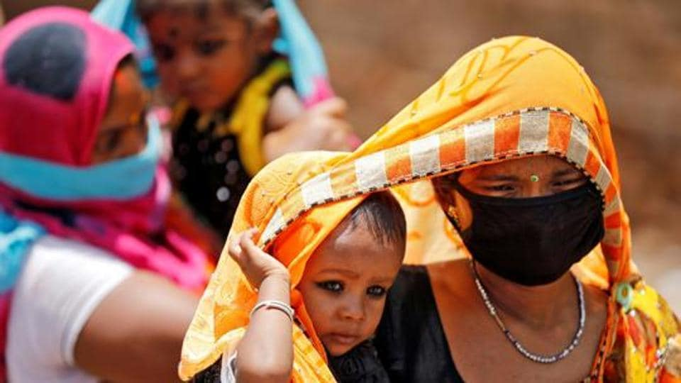 Migrant workers cover their children with saris to protect them from heat as they wait to get on a bus to reach a railway station to board a train to their home state of Bihar, Ahmedabad, May 20, 2020
