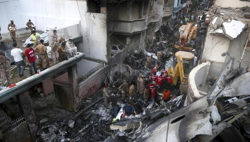Volunteers and soldiers look for survivors of a plane crash in a residential area of Karachi, Pakistan, May 22, 2020.