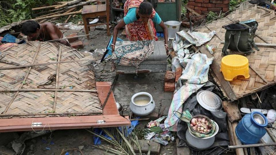 Residents salvage their belongings from the rubble of a damaged house in the aftermath of Cyclone Amphan in South 24 Parganas district in West Bengal on May 22, 2020.