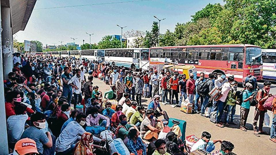 Migrant workers and families wait for transportation at the Ahmedabad railway station on Saturday.