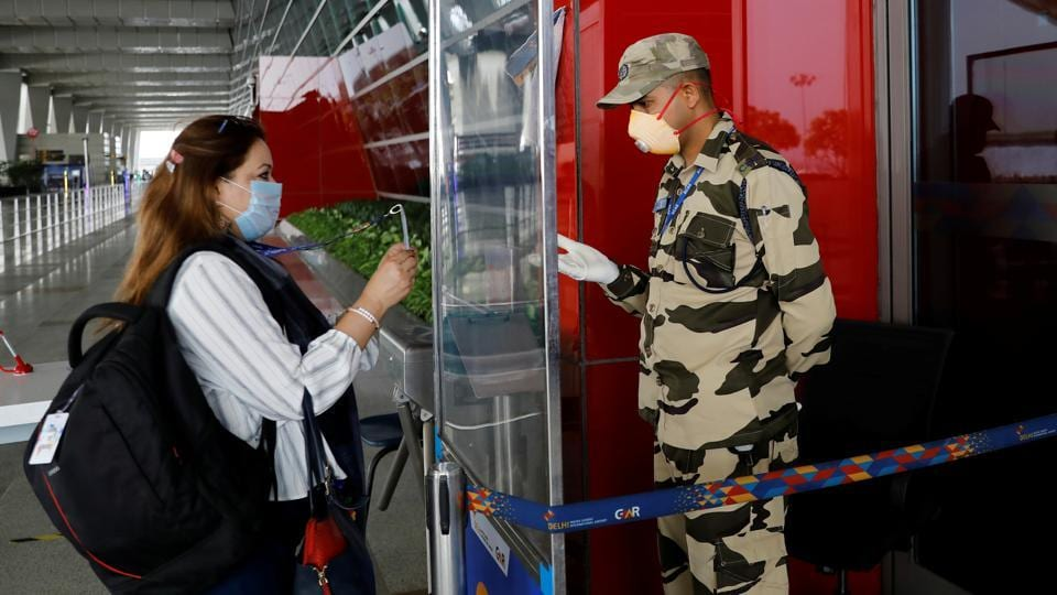 A Central Industrial Security Force personnel checks the identity card of a woman through a glass shield, ahead of the resumption of domestic flights from Monday.