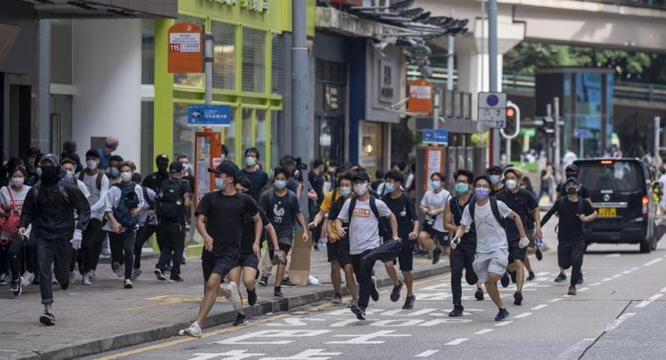 Demonstrators run from riot police during a protest against a planned national security law in Hong Kong, China, on Sunday, May 24, 2020.