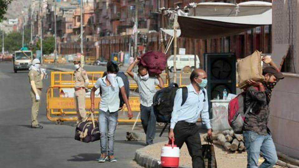 People carrying luggage pass barricades placed at the Ramganj coronavirus hotspot in Jaipur, Rajasthan, India on Monday, May 18, 2020.