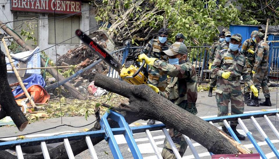 Army personnel cutting down and remove the uprooted trees from road aftermath of Cyclone Amphan in Kolkata on Sunday.