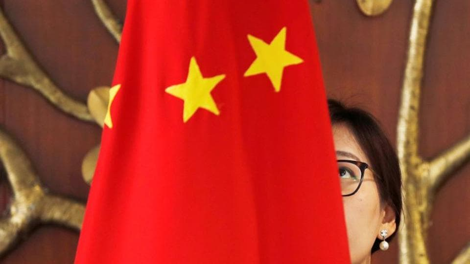 A Chinese official adjusts a Chinese flag before the start of a meeting in New Delhi, India.