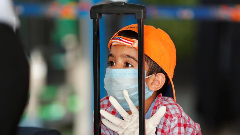 A child wearing a protection mask and gloves is seen at Indira Gandhi International (IGI) airport, after the government allowed domestic flight services to resume, during an extended nationwide lockdown to slow the spread of the coronavirus disease (COVID-19), in New Delhi.