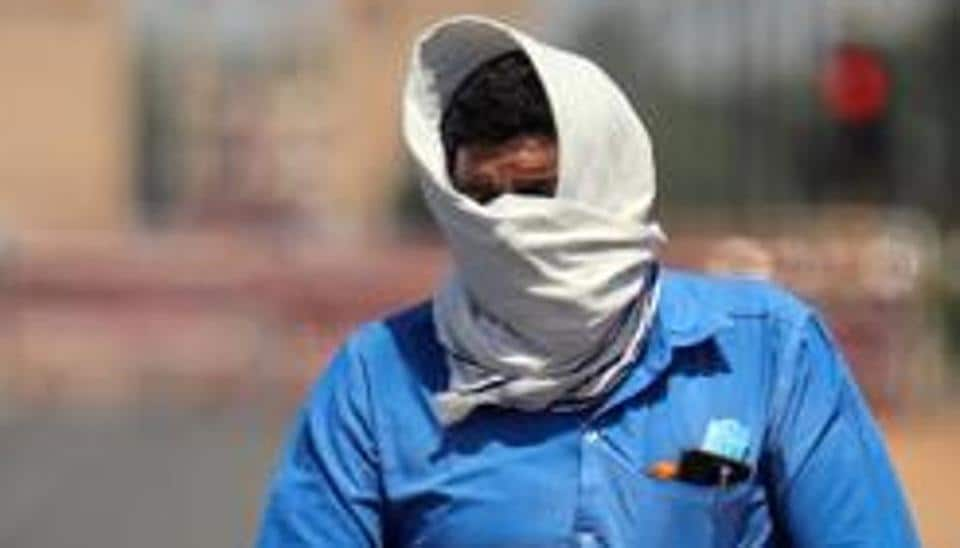 A man covers his face as he rides a bicycle during the heatwave in New Delhi on May, 25.