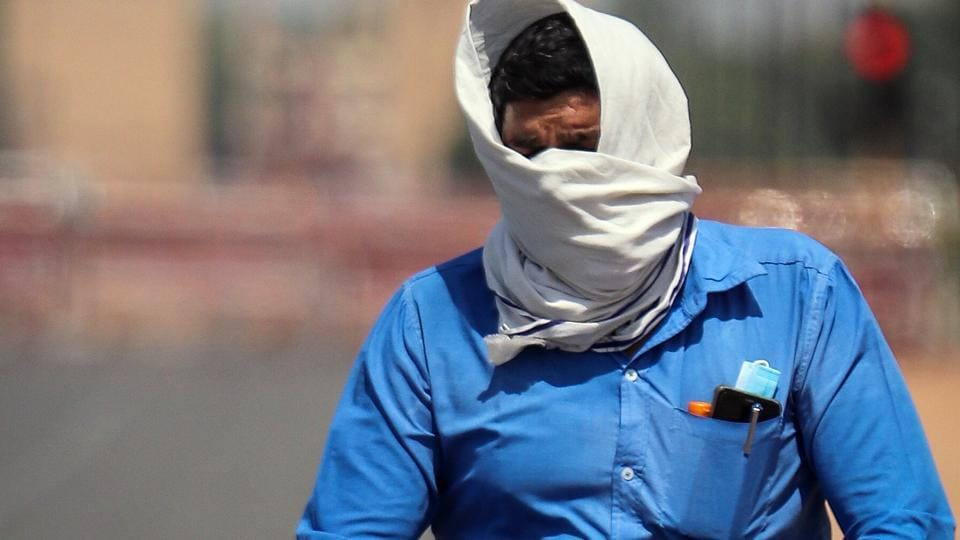 A man covers his face as he rides a bicycle during the heatwave in New Delhi on Monday.