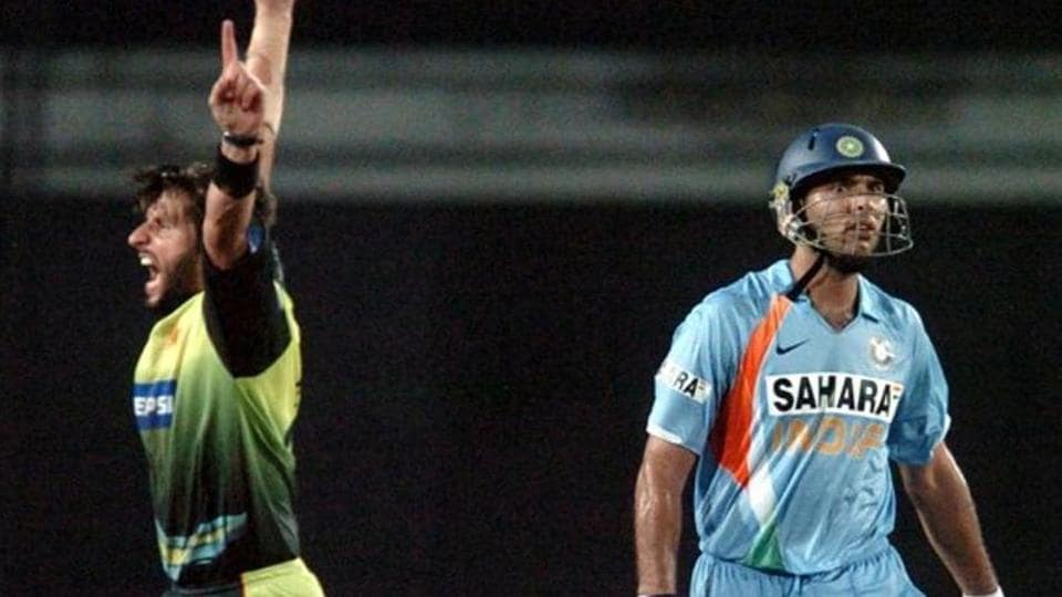 Pakistani cricketer Shahid Afridi (L) celebrates the dismissal of Indian cricketer Yuvraj Singh (R)