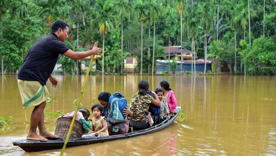 Villagers use a country boat to shift from a flooded locality following heavy rainfall at Bolbola in Goalapra district of Assam, Monday, May 25, 2020.