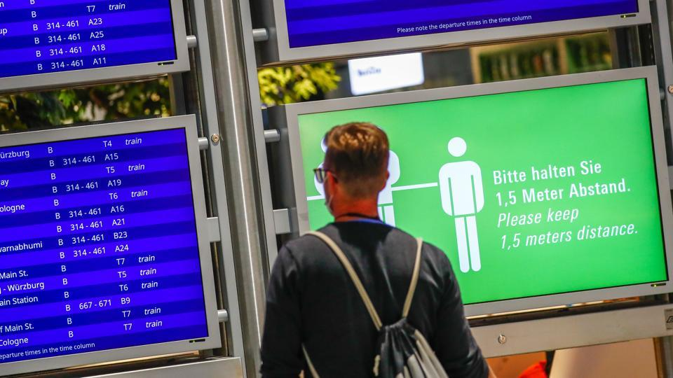A social distancing sign sits beside flight departure information screens at Frankfurt Airport.