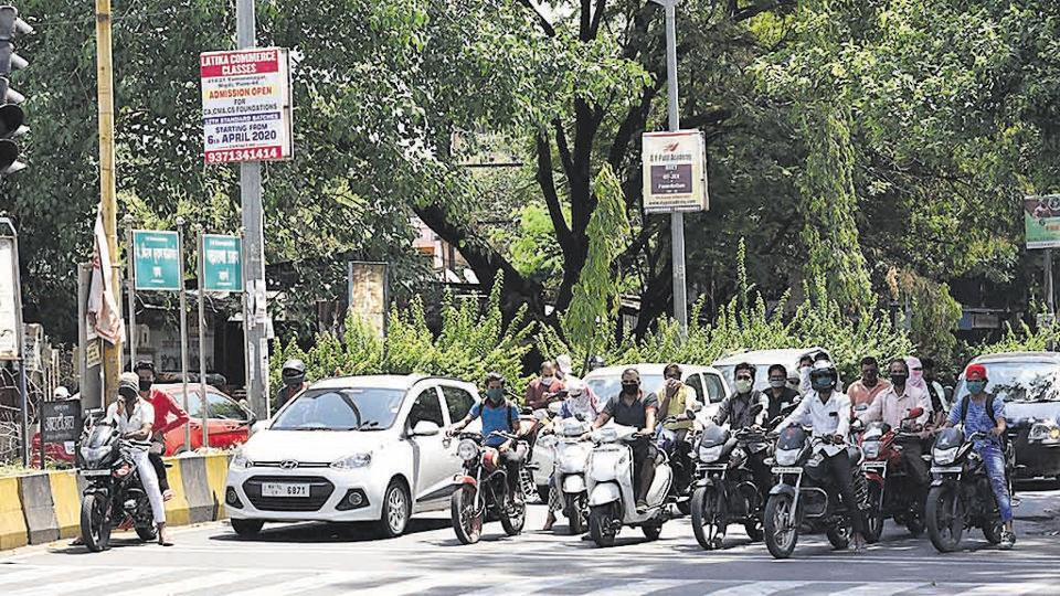 People wait at a traffic signal in Pimpri-Chinchwad on Monday.