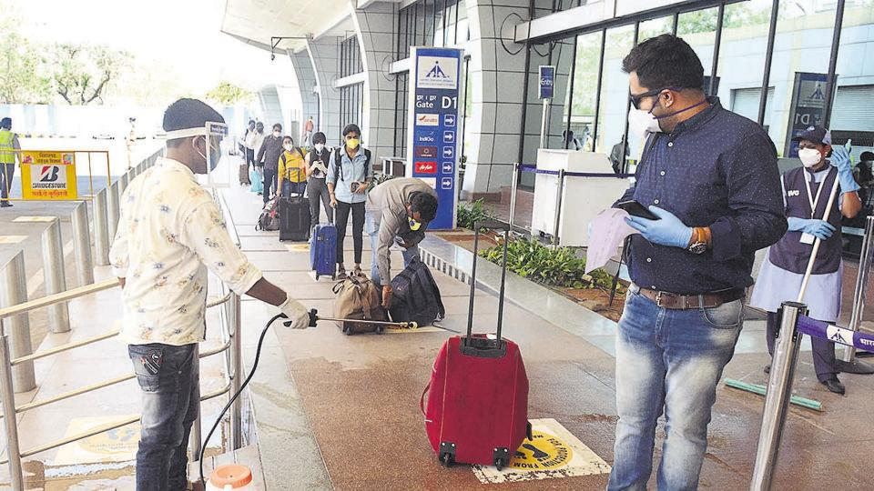 A worker sprays disinfectant on the bag of a passenger at Pune airport, as commuters are seen maintaining social distance. On Monday, the domestic commercial flights resumed after being grounded for almost two months due to the Covid-19 pandemic.