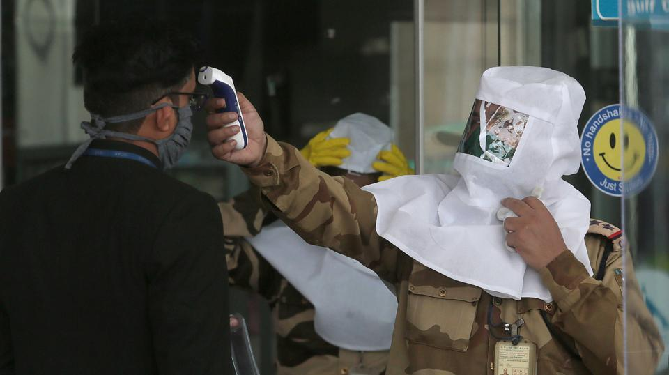 CISF personnel in PPE headgear thermal screens an airport staff as expatriates from Rajasthan.