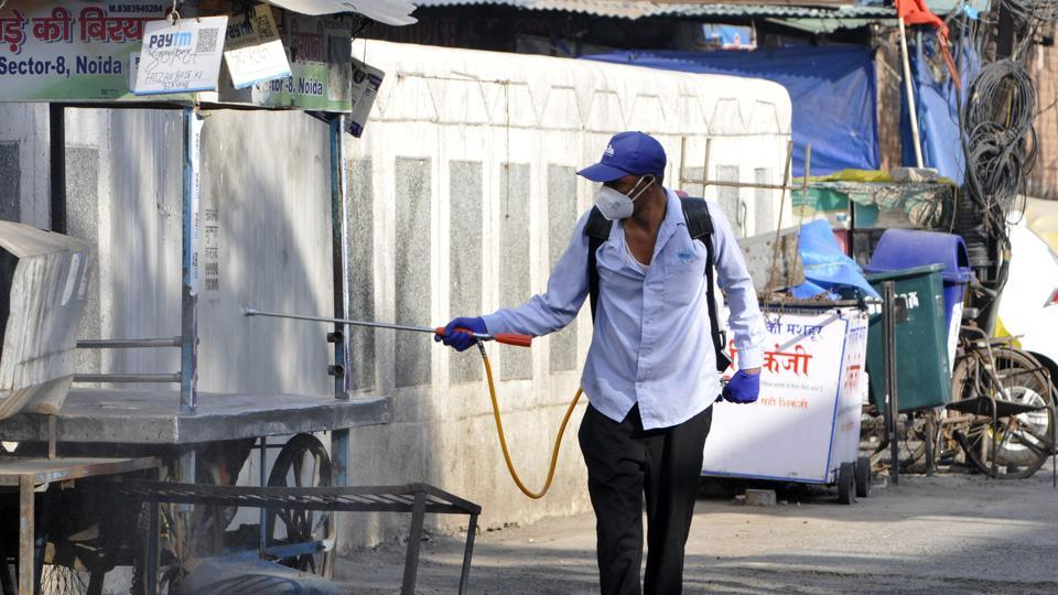 A personnel disinfects an area in a coronavirus hotspot at Sector 9, Noida