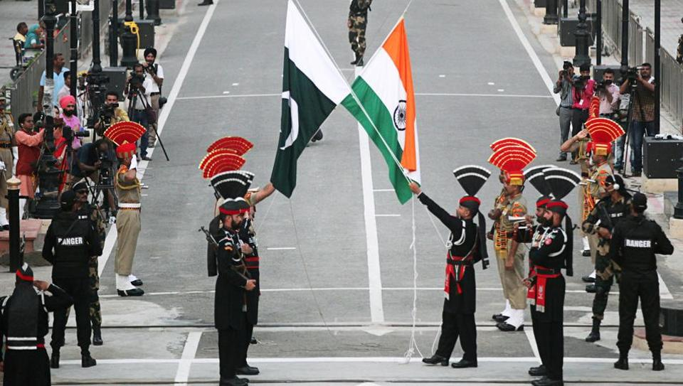 Pakistani Rangers (wearing black uniforms) and Indian Border Security Force (BSF) officers lower their national flags during parade on the Pakistan's 72nd Independence Day, at the Pakistan-India joint check-post at Wagah border, near Lahore, Pakistan.