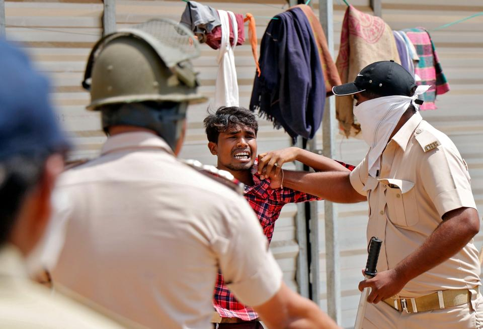 A migrant worker reacts as he is detained by police during a protest by migrant workers demanding to return to their home states, during an extended nationwide lockdown to slow the spreading of the coronavirus disease (Covid-19), in Ahmedabad, India.