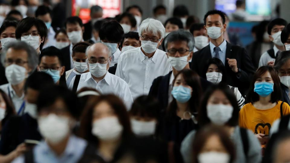 People wearing protective masks make their way during rush hour at Shinagawa station on the first day after the Japanese government lifted the state of emergency in Tokyo, Japan on May 26, 2020.