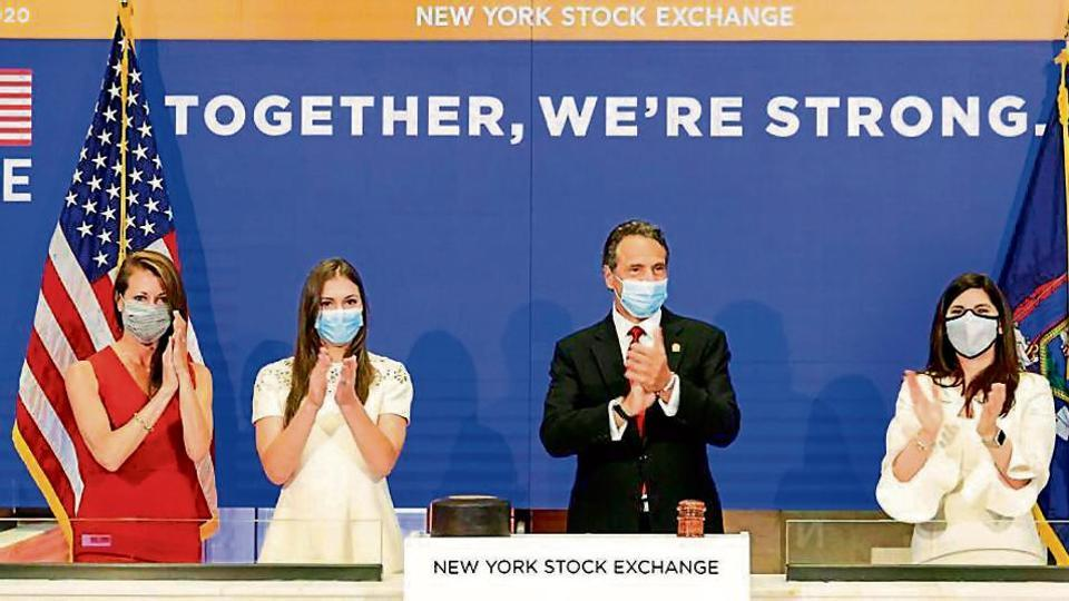 New York State Governor Andrew Cuomo (centre) applauds as he rings the opening bell of the New York Stock Exchange with NYSE president Stacey Cunningham (right) on Tuesday.