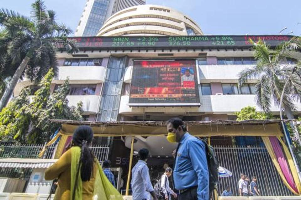 A man walks with a mask beside the building of the Bombay Stock Exchange, Mumbai, March 13, 2020
