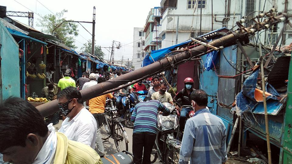 Commuters face hurdles while crossing a road due to an electric pole which was uprooted by Cyclone Amphan, at Hooghly in Kolkata on Tuesday.