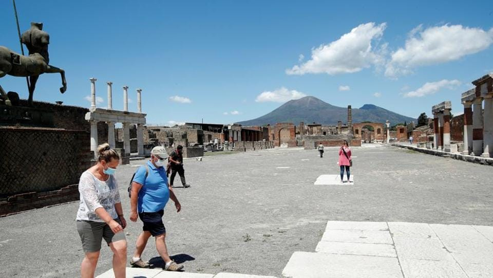 Italian tourists wearing protective face masks visit the archaeological site of the ancient Roman city of Pompeii as it reopens to the public with social distancing and hygiene rules, after months of closure due to an outbreak of the coronavirus disease (COVID-19), in Pompeii, Italy, May 26, 2020. REUTERS/Ciro De Luca