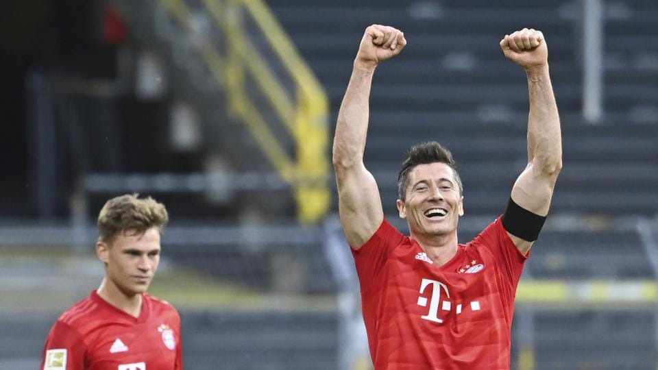 Munich's Joshua Kimmich, left, looks on as his teammate Robert Lewandowski, right, celebrates after the German Bundesliga soccer match between Borussia Dortmund and FC Bayern Munich in Dortmund, Germany, Tuesday, May 26, 2020.