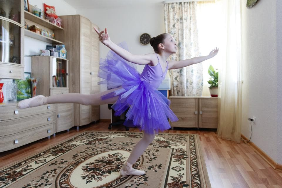 Alexandra Kustova, shows how she dances prior to an interview in her family's apartment in Yekaterinburg, a city in the Urals, Russia on Thursday, May 7, 2020. For 12-year-old Alexandra, self-isolation during the coronavirus pandemic turned out to be a blessing in disguise. Now that all the studies are conducted online, not only does she have more time for her two favorite hobbies _ ballet and jigsaw puzzles _ she spends more time with her family and helps out her grandmother, who lives in the same building two floors down. (AP Photo/Anton Basanaev)