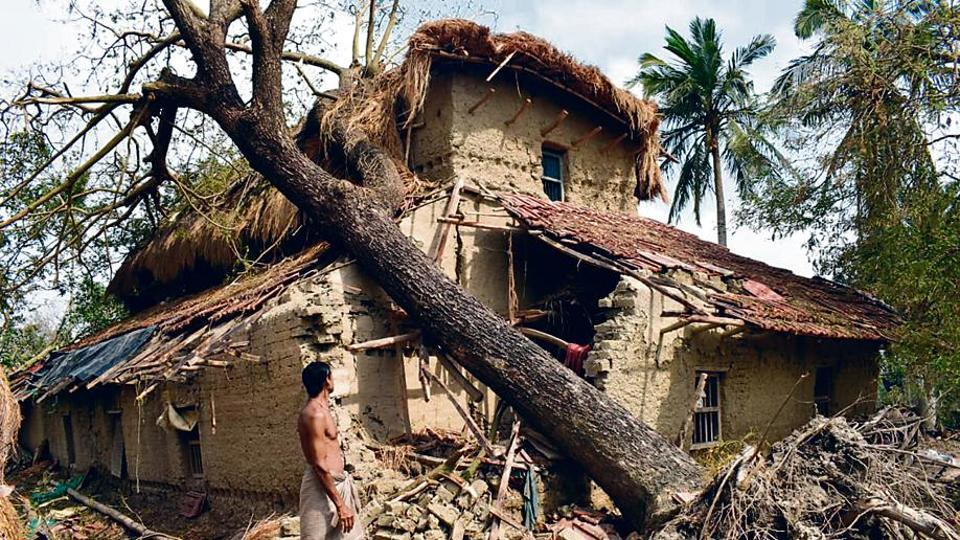 A man stands next to a house damaged in Cyclone Amphan in Sunderbans region's Sagar island.