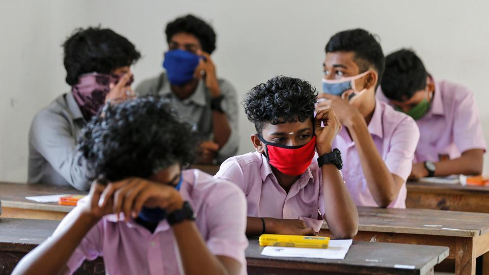 Students wearing protective masks wait for vocational higher secondary education exams which were postponed amid the coronavirus disease (COVID-19) spread, inside a school in Kochi, India.