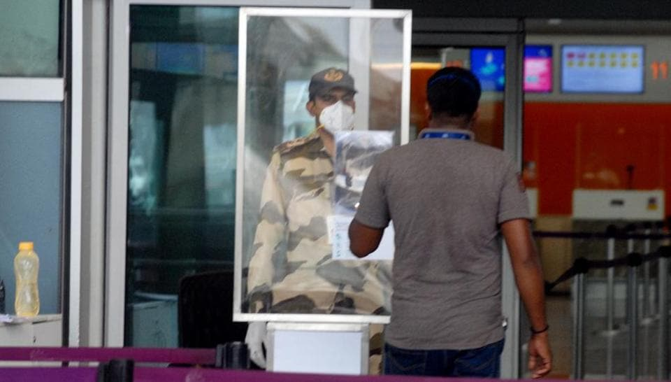 A security man checks the ID of staff before entering the Kempe Gowda International Airport following the resumption of domestic airline services from tomorrow, in Bengaluru on Sunday.