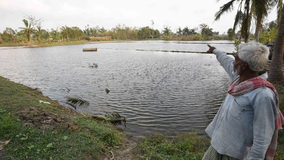 A man points towards a pond filled with saline water that has killed fresh water fish and was brought upstream due to Cyclone Amphan, at Kakdwip in the Sunderbans, South 24 Parganas district, West Bengal, India on Frisday, May 22, 2020.