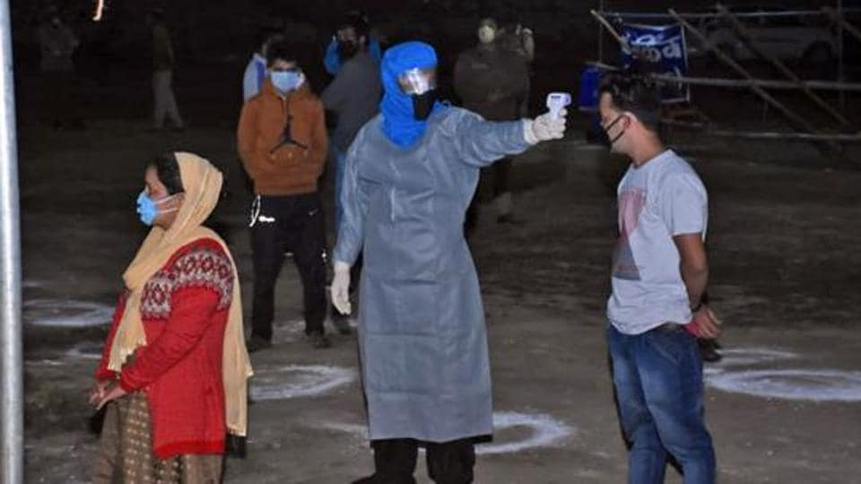 Migrants from Uttarkashi undergo thermal screening as they arrive at Chinyalisour by government buses during a government-imposed nationwide lockdown as a preventive measure against the coronavirus, in Uttarkashi on May 9.