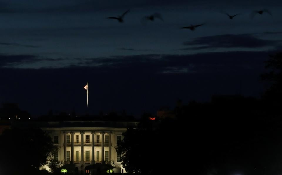 Geese fly as dusk falls behind the south side of the White House as the coronavirus disease (COVID-19) outbreak continues in Washington, US. The death toll from the coronavirus disease in the US surpassed 100,000 people earlier in the day.