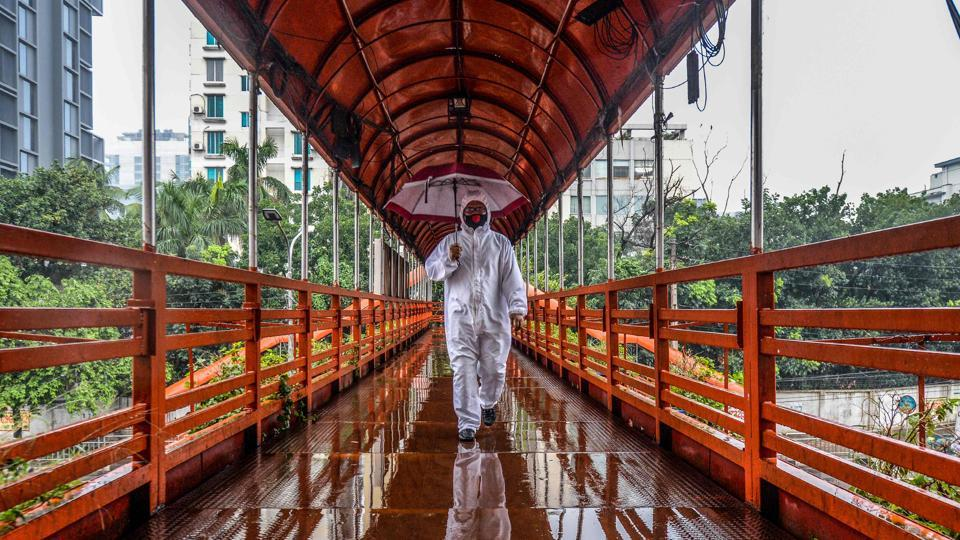 A man wearing protective gear as a preventive measure against the Covid-19 coronavirus walks over a footbridgein Dhaka on May 27, 2020. (