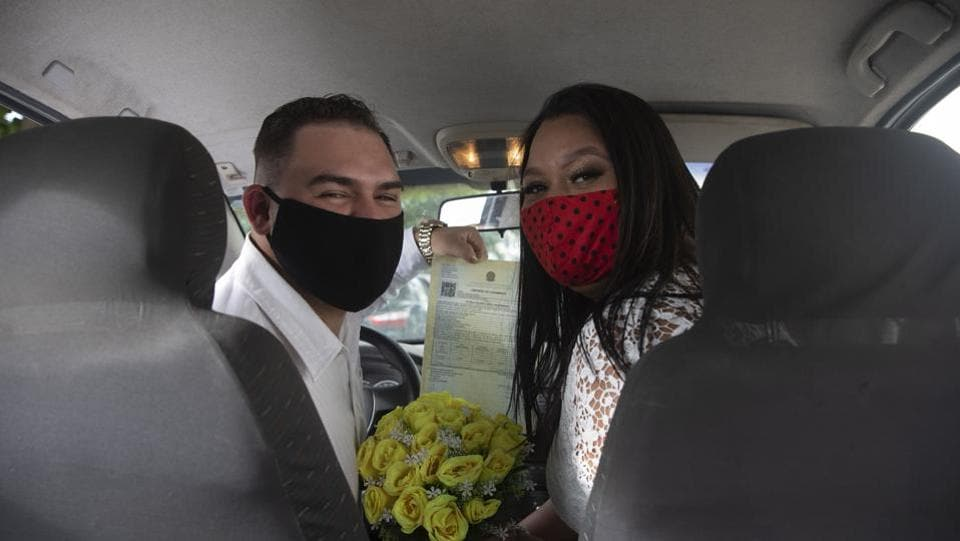 Ayrton (L) and Natasha (R) wearing masks, pose for a photo after their drive-thru wedding at the registry office in Santa Cruz, a neighbourhood on the western outskirts of Rio de Janeiro, Brazil. The drive-thru marriage perhaps wasn't the most romantic thing people had planned for themselves, but it is a viable option in these times. (AP)