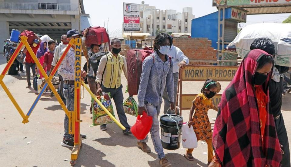 Migrant workers and their families standing in a queue wait for buses to move towards the railway station to board a train to their home state Bihar, during nationwide lockdown to slow the spreading of the coronavirus disease (COVID-19), in Ahmedabad on May 22/ representative.