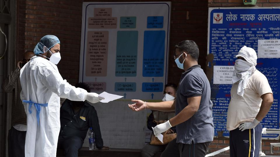 Medical workers in PPE gear interact with visitors outside the Covid-19 ward, at Lok Nayak Jai Prakash Narayan Hospital, in New Delhi, Saturday, May 30, 2020.
