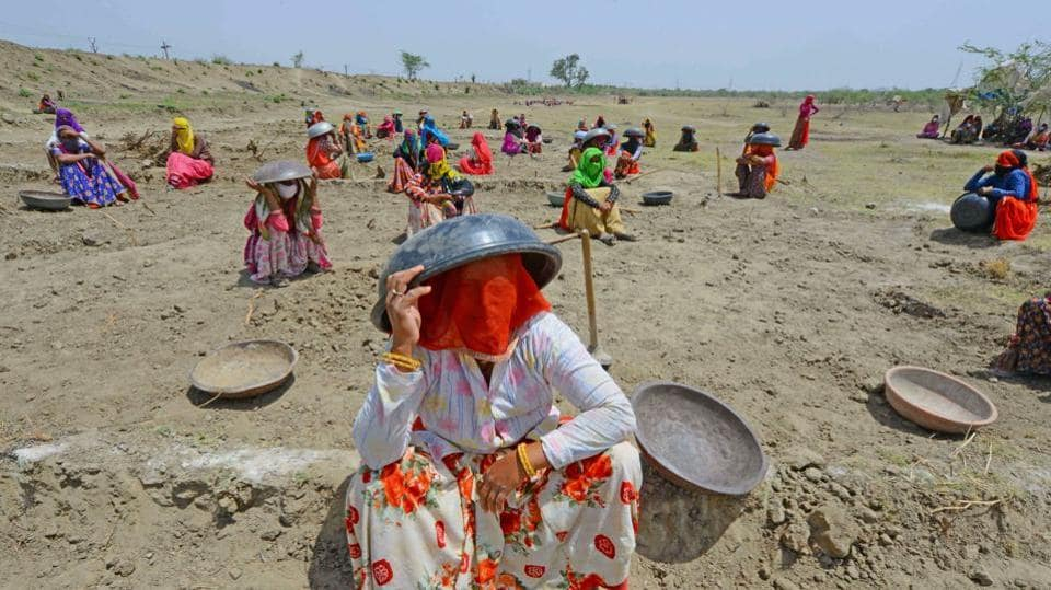 Labourers under MNREGA use mortar pans to protect themselves against the scorching sun, at a worksite on the outskirts of Beawar, Rajasthan on May 29. A heatwave sweeping through North and central India this week had mercury hitting 50 Celsius in Rajasthan. Parts of Delhi recorded their hottest May temperatures in over a decade. (PTI)