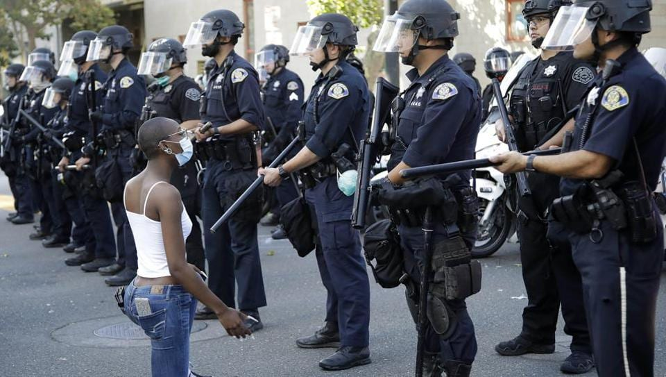 A masked protester kneels before the San Jose police on May 29, California, in response to the death of George Floyd in police custody on Memorial Day in Minneapolis. The police officer seen on video kneeling on the neck of George Floyd, who died in custody after pleading that he could not breathe, was arrested on May 29 after three days of protests. (AP)