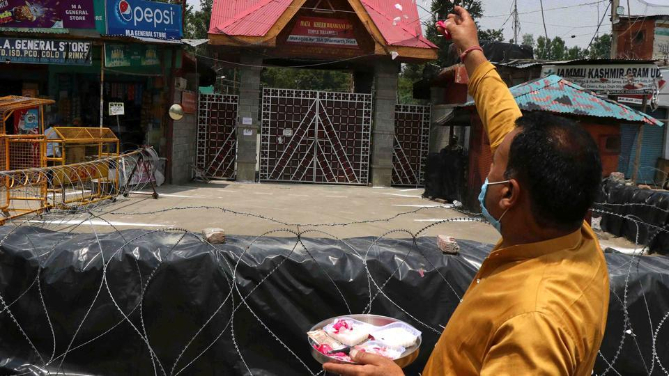 A man prays and makes an offering at the entrance to the Kheer Bhawani temple at Tulmulla in Ganderbal with no congregation held on the occasion of Mela Kheer Bhawani due to lockdown restrictions in Ganderbal, Jammu and Kashmir.
