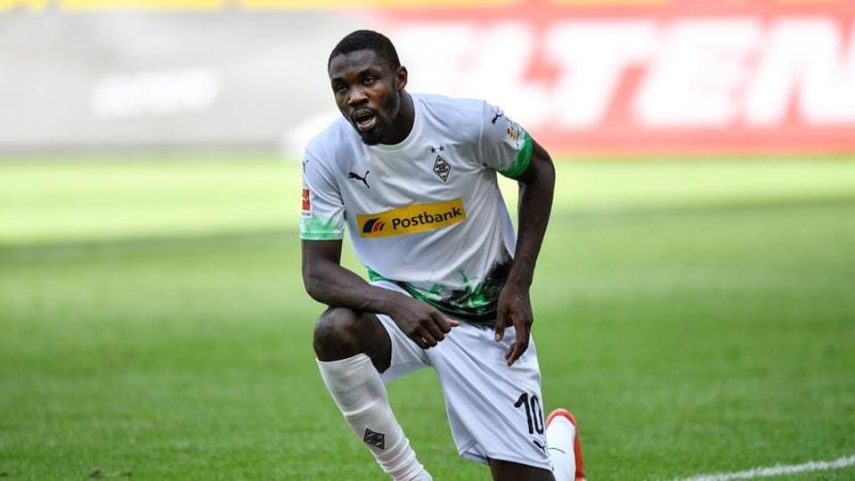 Borussia Moenchengladbach's Marcus Thuram kneels after celebrating their second goal.