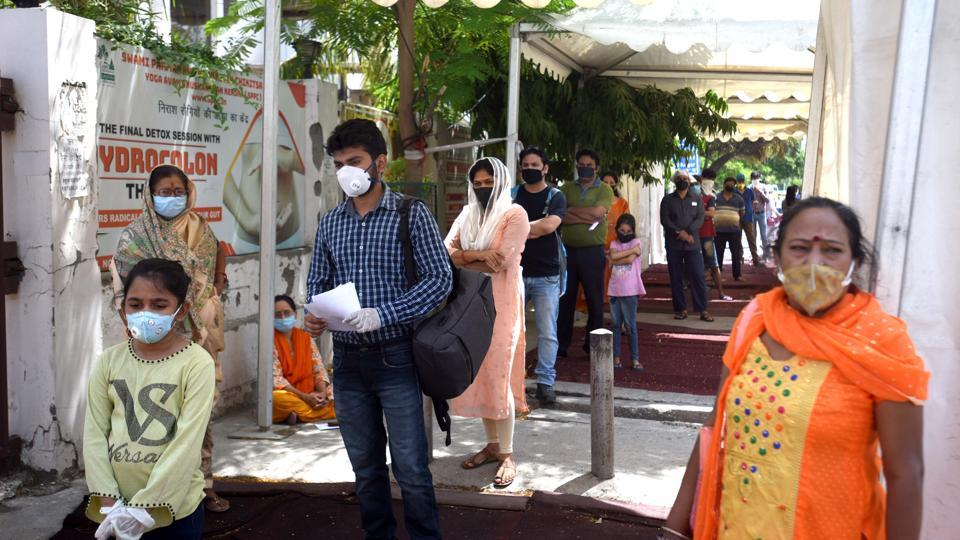 People stand in queue to get screened for coronavirus, at SPPC Hospital in Vinod Nagar New Delhi on Saturday.