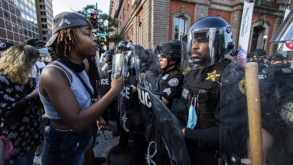 Demonstrators talk to police in riot gear.