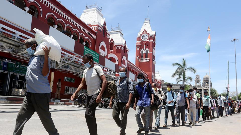 Stranded migrant labourers queue to board a special train to Bihar from Chennai Central railway station