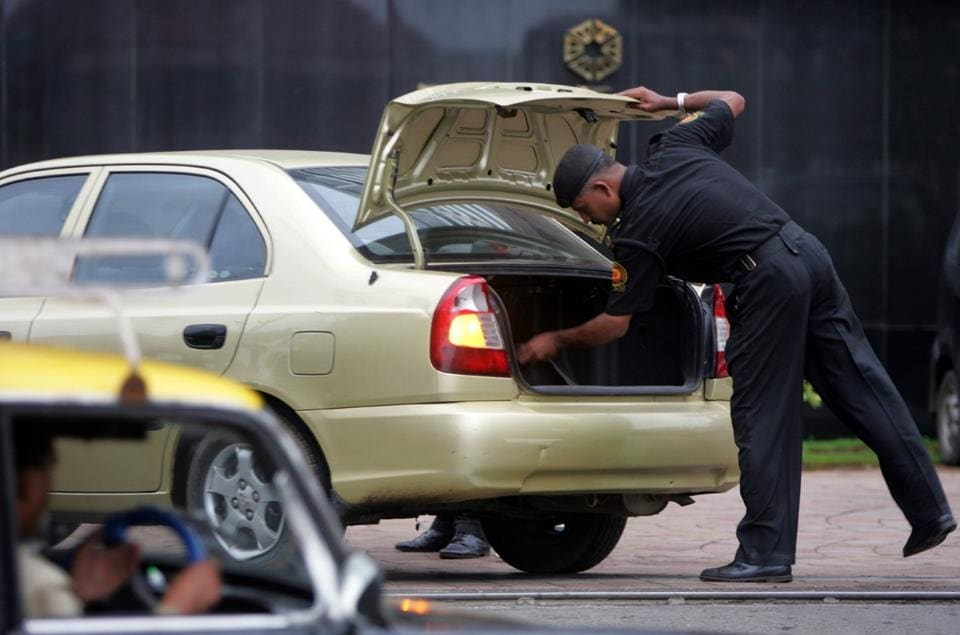 Outsourcing law and order:Security guards inspect a vehicle after warnings of a possible terrorist attack in Mumbai in August 2006.