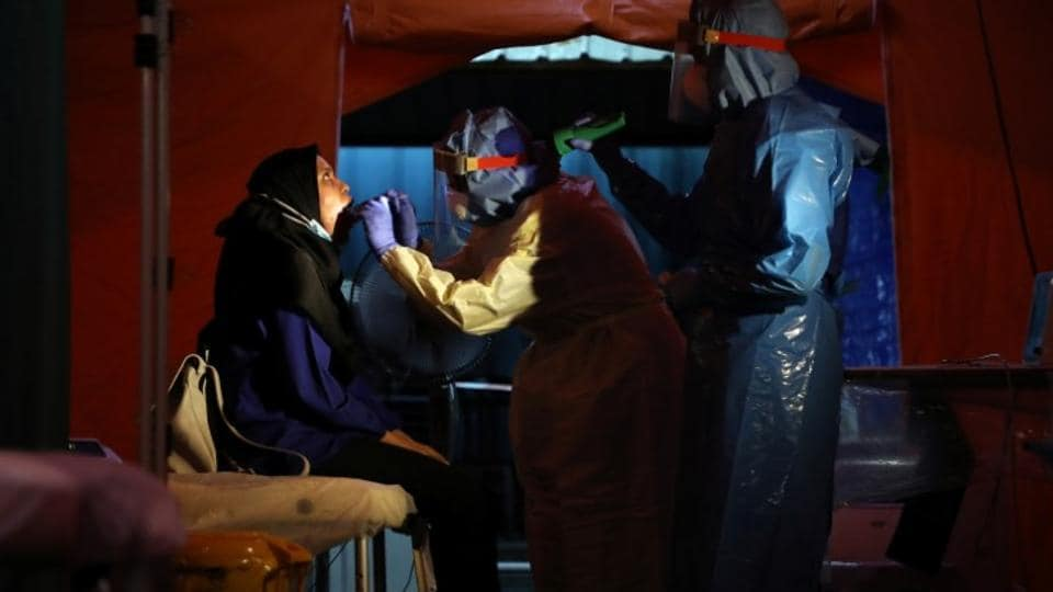 Health workers get a swab from a woman in a makeshift centre tent set up in the Kuala Lumpur Hospital parking lot, amid the coronavirus disease (COVID-19) outbreak, in Kuala Lumpur. (Representational Image)