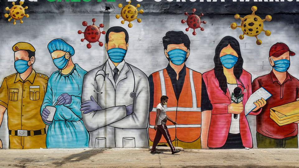 A man walks in front of a wall of graffiti paying salute to front line corona warriors in New Delhi on May 31. The Delhi government has attributed the higher number of cases May 28 onwards to the number of Covid-19 samples being processed per day.  (Manvender Vashist / PTI)