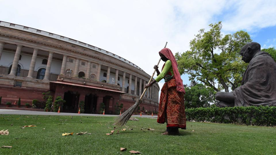 A worker cleans the lawn at Parliament House, during the nationwide lockdown in the wake of coronavirus pandemic, in New Delhi.